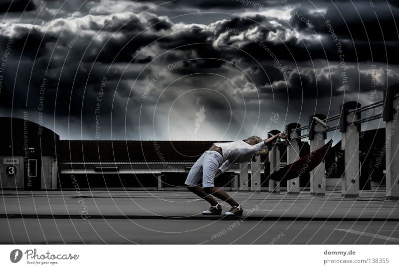 bullettime Woman Stand Flying Umbrella Apocalypse Park Parking level Parking garage Wall (barrier) Clouds Town Rain Threat Blonde White Black Dark Bend Gale