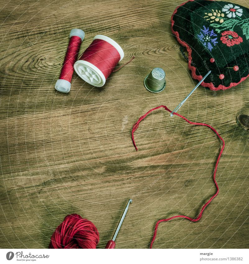 Threaded in red: Sewing equipment, such as needle, thread, thimble wool, crochet hook and a needle cushion on a wooden table Leisure and hobbies Handcrafts Knit