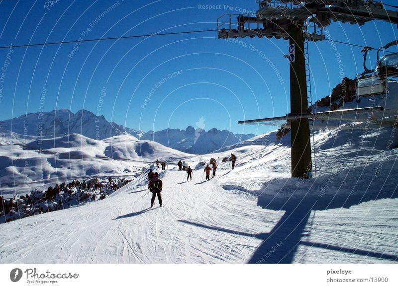 Human being Sky Mountain Snow Sports Skiing Downward Blue sky Coil Ski lift Ski run Chair lift Downward slide Pole Ski-run