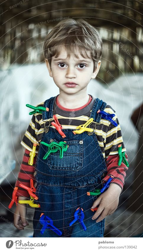 boy Child Blonde Stripe T-shirt Toddler sad sadness play playful hair blue Jeans clamp toy childhood face eyes caucasian looking serious standing cute