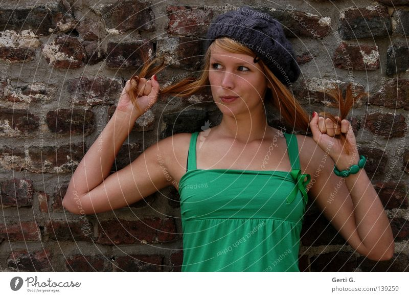 And now what? Woman Young woman Beautiful Green Long-haired Red-haired Cap T-shirt Facial expression Hand Bracelet Wall (barrier) Wall (building) Grimace