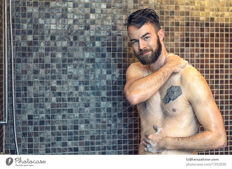 Friendly young man soaping himself in the shower Skin Face Wellness Bathroom Man Adults Beard Smiling Wet Clean at camera bath bathing care Caucasian chest
