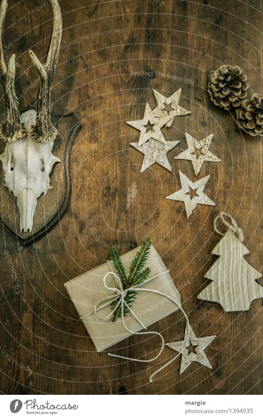 Merry Christmas! One present, five stars a Christmas tree - pendants, two pine cones and antlers hang on a wooden wall Hunting Living or residing Decoration