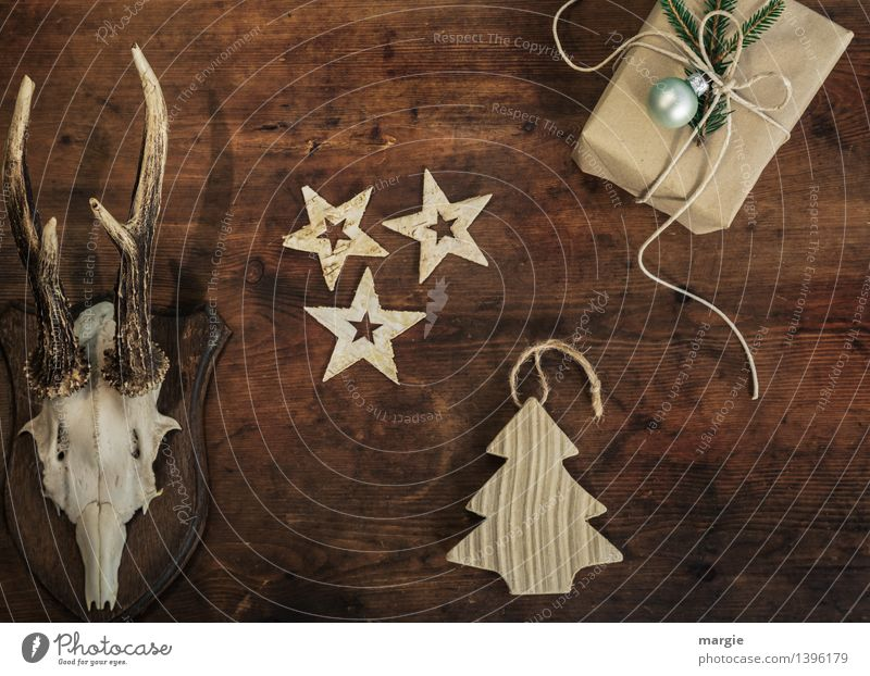 Merry Christmas! A present, three stars a Christmas tree - pendants and antlers hang on a wooden wall Leisure and hobbies Living or residing Decoration Tree