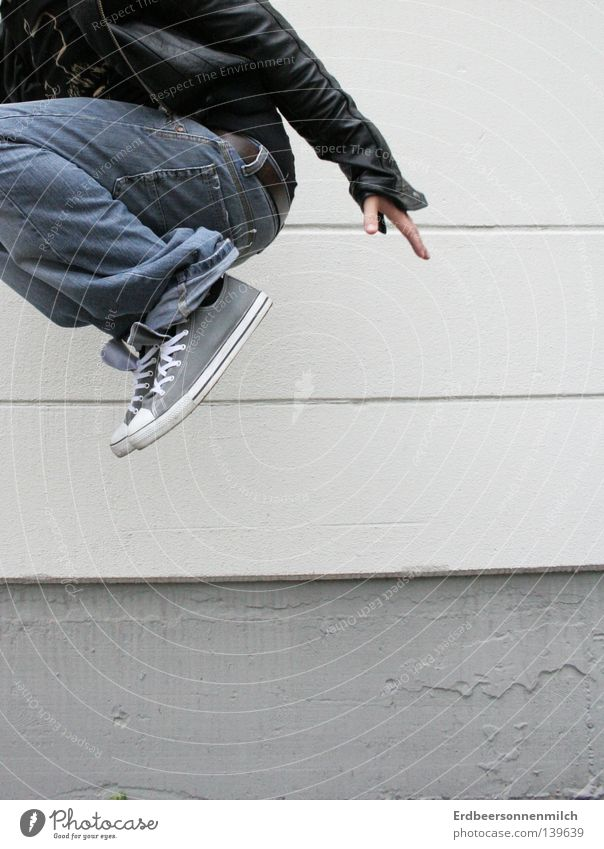 Where are you going? Jump Gray Chucks Wall (building) Man Leather jacket Distress Joy Media Guy Industrial Photography happy Life Jeans Fear Partially visible