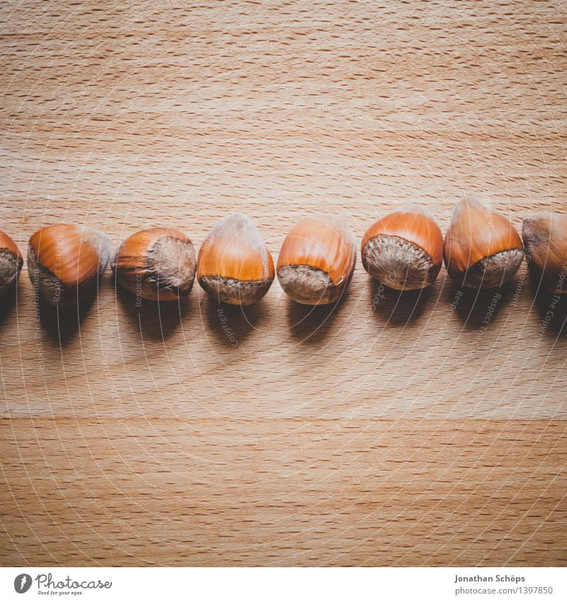 Hazelnuts on a wooden table in a row Food Nutrition To have a coffee Picnic Organic produce Vegetarian diet Slow food Finger food Esthetic Brown Hazel brown