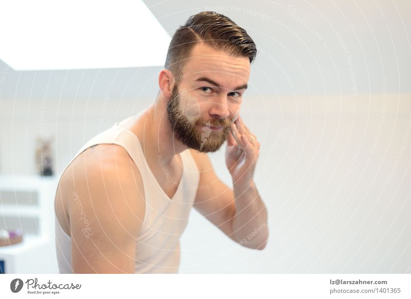 Young man applying shaving cream Face Cream Mirror Bathroom Man Adults Hand Beard Smiling Friendliness Clean Precision appearance care Caucasian Cheek