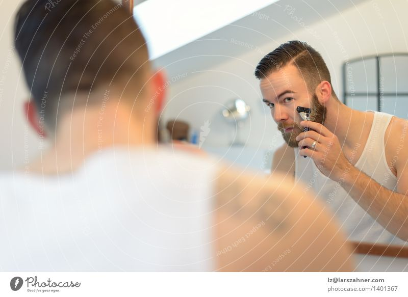 Young man shaving above his beard Face Mirror Bathroom Man Adults Beard Clean Precision appearance care Caucasian Cheek concentrating focusing getting ready