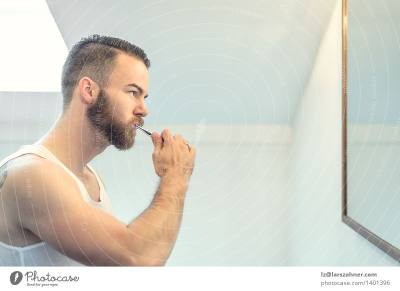 Young bearded man brushing his teeth Face Health care Mirror Bathroom Man Adults Teeth Beard Toothbrush Modern Clean caries cleaning cleanliness Dental