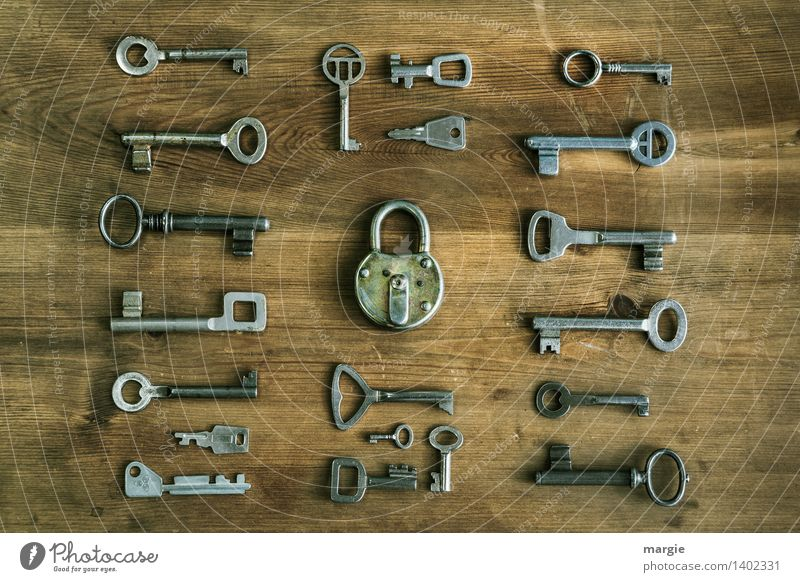 Which one fits? Many different keys are arranged around a door lock Locksmith Technology Key Padlock Collection Wood Metal Brown Black Concern Close Undo