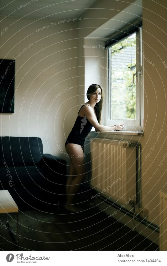 young woman in black body stands at the window and looks into the camera Athletic Well-being Contentment Young woman Youth (Young adults) Legs 18 - 30 years