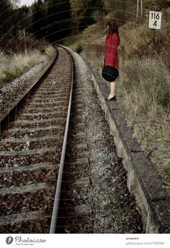 116 Freedom Woman Adults Nature Autumn Forest Platform Railroad tracks Coat Hat Stone Red Loneliness Reunion Forget Station Colour photo Subdued colour