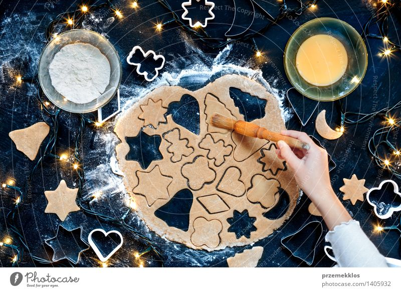 Girl making the Christmas cookies Table Kitchen Human being Hand 1 Make Cut Cutter Knife Egg Flour Gingerbread Home-made Preparation Colour photo Interior shot