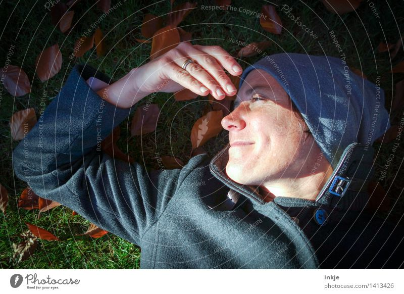Woman with cap lies in autumn leaves Lifestyle Well-being Contentment Senses Relaxation Calm Leisure and hobbies Adults Face Hand 1 Human being 30 - 45 years