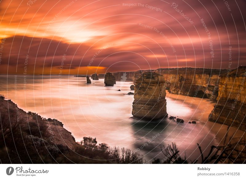 Twelve Apostles in the Evening Red Landscape Clouds Sunrise Sunset Rock Waves Coast Beach Bay Ocean Great Ocean Road Cliff Discover Relaxation Vacation & Travel