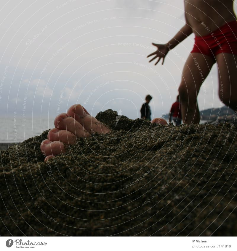 Look, Mama, I found something here.... Beach Child Feet Hand Sand Bury Find Frightening Scare Dangerous Earth buried