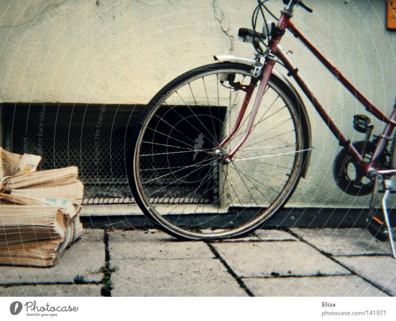 left Sidewalk Bicycle Newspaper Old Yellowed Tire Spokes Grating Wall (building) Flow House (Residential Structure) Parking Magazine Detail. cellar window wean