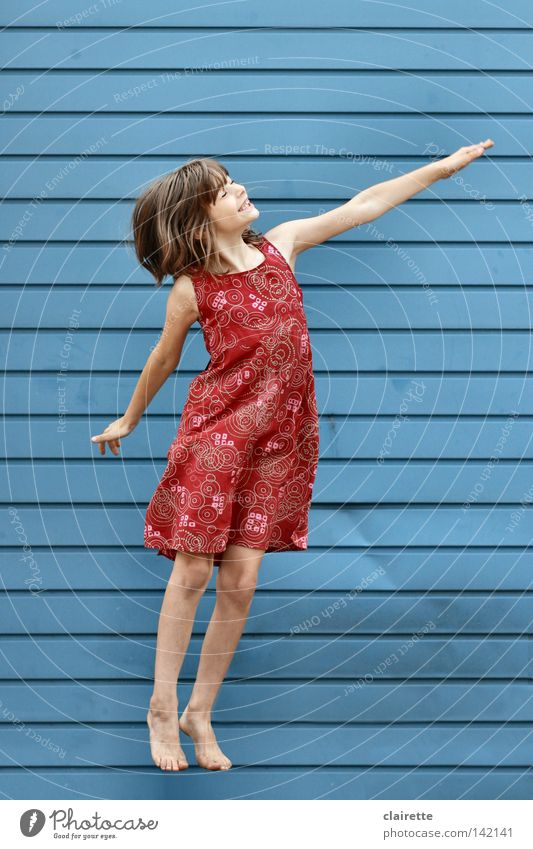 Supergirl takes off Colour photo Multicoloured Exterior shot Full-length Half-profile Closed eyes Joy Child Girl Dress Flying Jump Blue Red Floating Superman