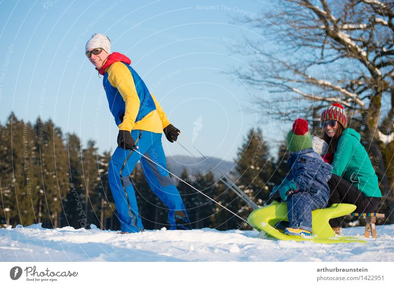 Family in winter Joy Athletic Tourism Trip Winter Snow Winter vacation Sleigh Human being Masculine Feminine Child Young woman Youth (Young adults) Young man
