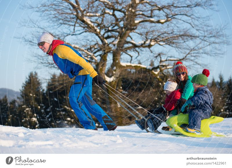 Young sporty couple with children at the sledge in winter in sunshine Joy Leisure and hobbies Sleigh Vacation & Travel Tourism Winter Winter vacation