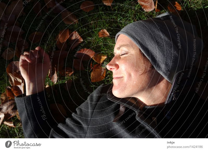 Close-up Smiling woman lying in autumn leaves Lifestyle Harmonious Well-being Contentment Senses Relaxation Calm Leisure and hobbies Woman Adults Face 1