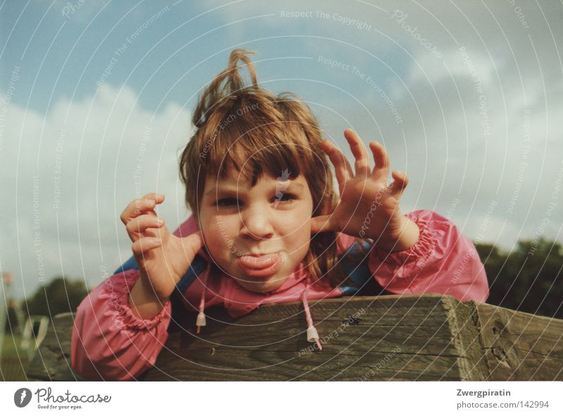 childhood Child Small Brash Grimace Girl Tongue Stick out Rain jacket Pink Blue Playground Sky Clouds Gray Closed White Wood Brown Arrangement Texture of wood