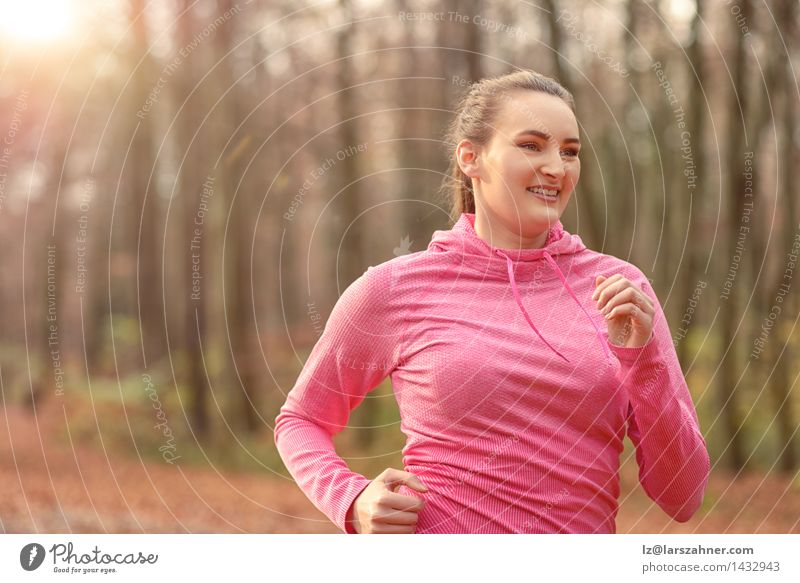 Pretty fit young woman jogging in woodland Diet Lifestyle Body Face Sports Jogging Woman Adults Nature Autumn Forest Brunette Fitness Smiling Fresh athletic