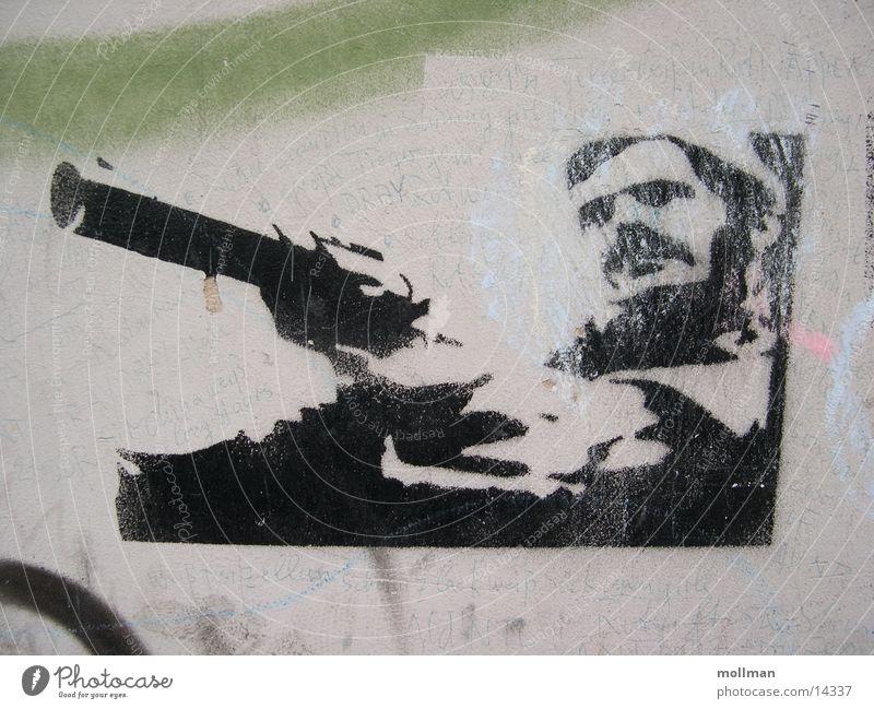 Stencil / Grafitti Masculine Adults Film industry Video Power Handgun Photographic technology graffiti Colour photo Long shot