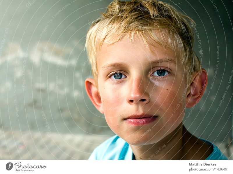 innocent lamb Small Child Blonde Disheveled Timidity T-shirt Background picture Wall (building) Plaster Asphalt Caught by a speed camera Red Flushed Calm Break