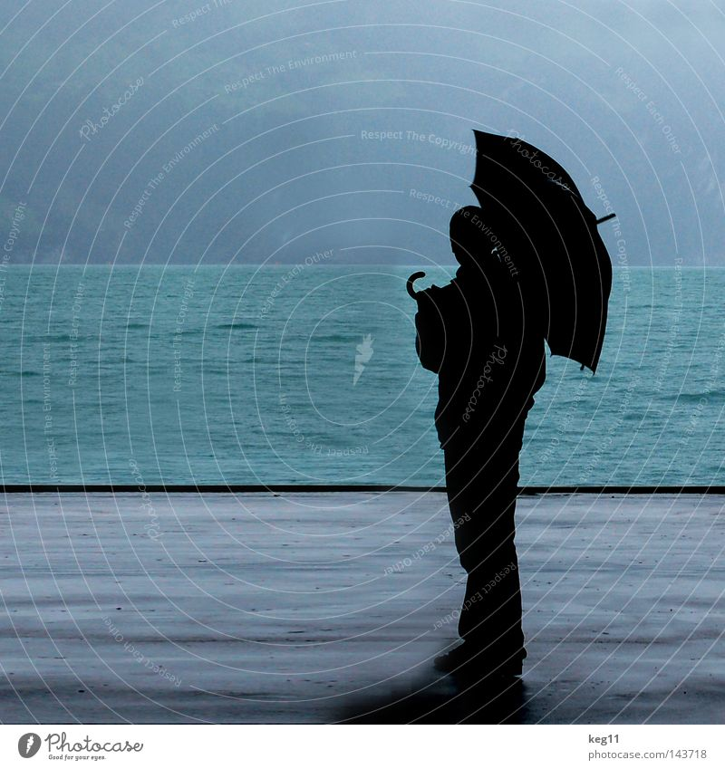 Dancing in the Rain Switzerland Lake Water Ocean Umbrella Drops of water Bad weather Roof Rain jacket Man Loneliness Blue Gray Sky 3 Human being Silhouette