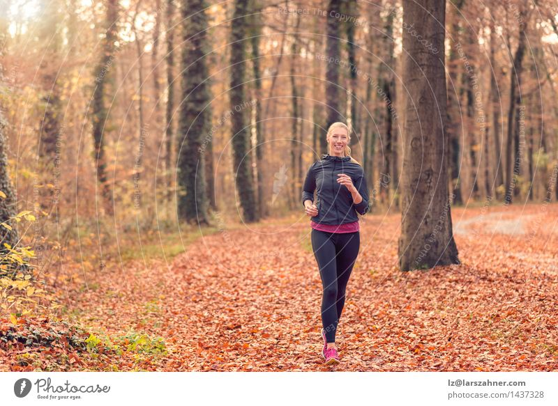 Pretty fit young woman jogging in woodland Diet Lifestyle Body Face Sports Jogging Woman Adults Nature Autumn Forest Blonde Fitness Smiling Fresh athletic