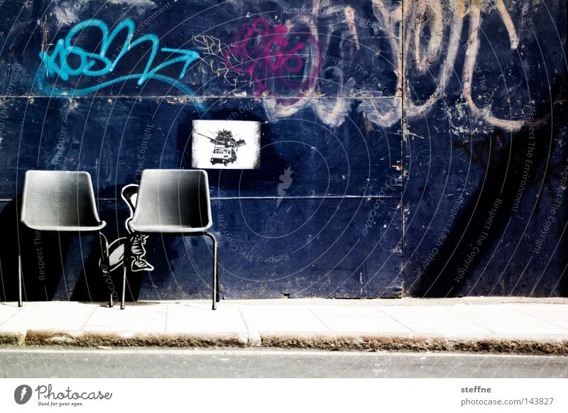 Take a seat Chair Stool Seating Wall (building) Street Gate Graffiti Traffic infrastructure Furniture