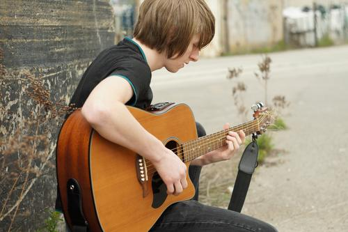 Young man with guitar Human being Masculine Youth (Young adults) 1 18 - 30 years Adults Emotions Moody Guitar Music Make music Sing Sit wood Acoustic