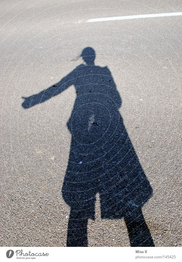 the hitchhiker Colour photo Exterior shot Shadow Silhouette Woman Adults Hand Beautiful weather Street Lanes & trails Stone Driving Gray Black Shadow play
