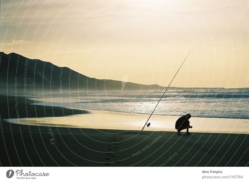la costa oeste 2 Beach Water Waves Sand Angler Human being Fishing rod Sky Coil Evening Cofete Fuerteventura Back-light Analog Leisure and hobbies Mountain