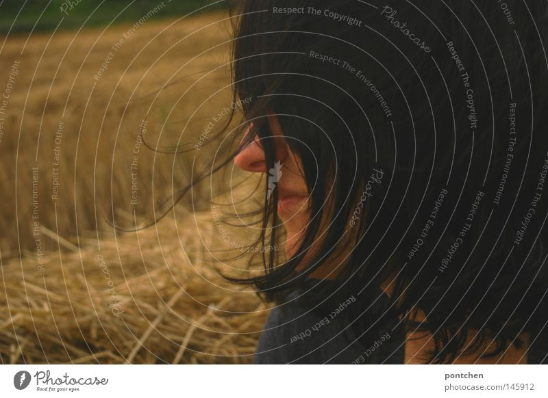 Half profile of a dark-haired woman in front of a mowed field of pontchen portrait Half-profile Hair and hairstyles Face Trip Feminine Young woman