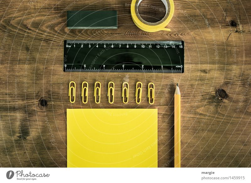 Landscape format; yellow black writing utensils, paper, notes, pencil, paper clips, adhesive tape, eraser on a wooden desk Education Study Professional training