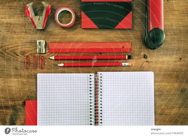 Landscape format: Red and black desk utensils on a wooden table. notebook, pencils, ruler, adhesive tape, sharpener, paper clips, book, stapler, staple monkey