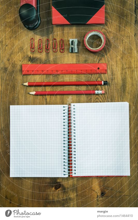 Red and black desk utensils on a wooden table. notebook, pencils, ruler, tape, sharpener, paper clips, book, stapler Education School Study Work and employment