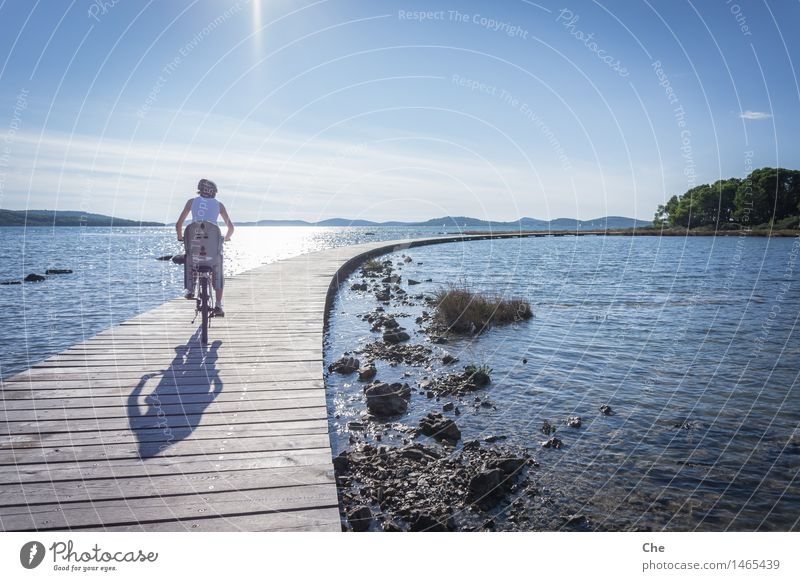over water Feminine 1 Human being 18 - 30 years Youth (Young adults) Adults Driving Bicycle Child seat Family & Relations Jetty Water Lake Ocean biking