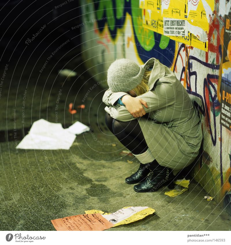 Sara Jane Woman Grief Sit Crouch Coat Tights Cap Woolen hat Graffiti Inscription Underpass Wet Cold Wall (building) Multicoloured Distress Lovesickness