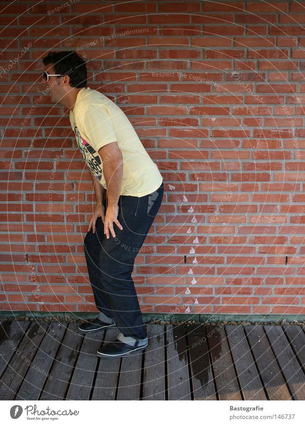 Human being Man Joy Yellow Wall (building) Laughter Stone Wall (barrier) Funny Wet Jeans Posture Hind quarters Toilet Pants Brick