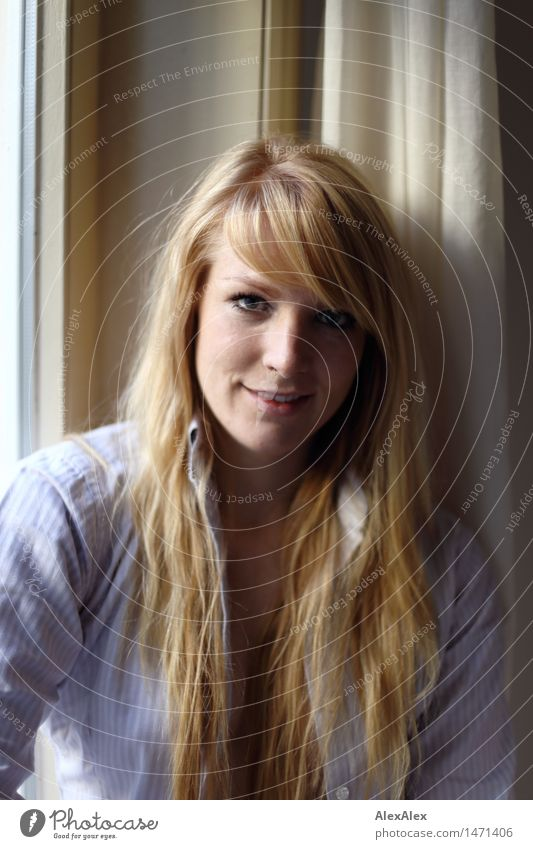 Portrait of a young blonde woman at a window pretty Harmonious Well-being Flat (apartment) Young woman Youth (Young adults) Hair and hairstyles Face