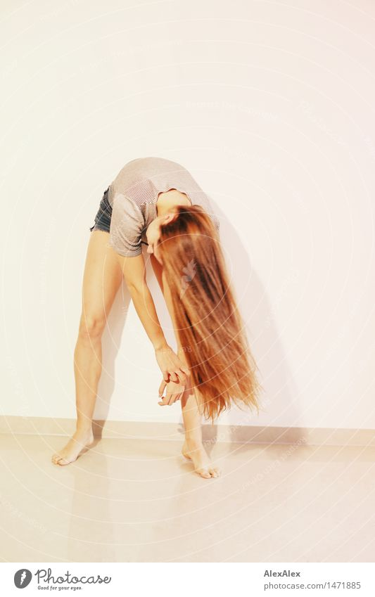 young, slim woman swings her upper body and her long, brunette hair in front of her legs, standing barefoot in front of a white wall Elegant Style pretty