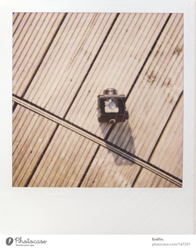 Lubitel Polaroid Speed Expensive Lomography Camera Take a photo Balcony Wooden floor Floor covering Wooden board Summer Shadow Minimalistic Furrow Across