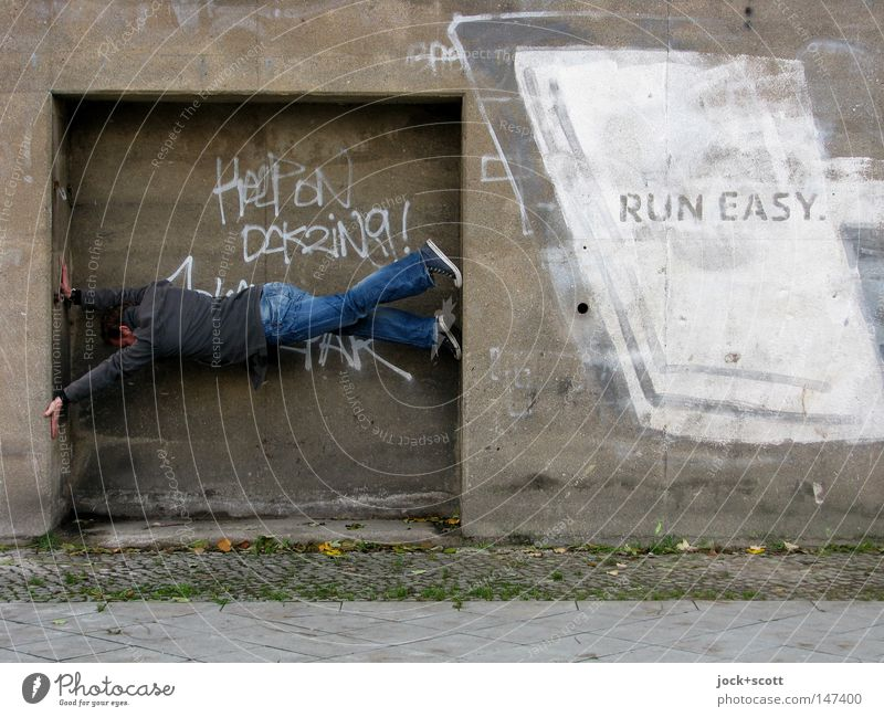 Human being Man Adults Graffiti Wall (building) Wall (barrier) Gray Characters Concrete Simple Posture To hold on Target Athletic Jeans Concentrate