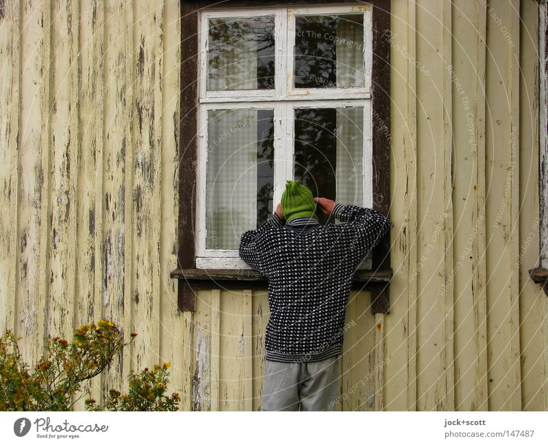 Human being Man Loneliness House (Residential Structure) Window Adults Wood Facade Bushes Authentic Wait Hope Search Desire Contact Cap