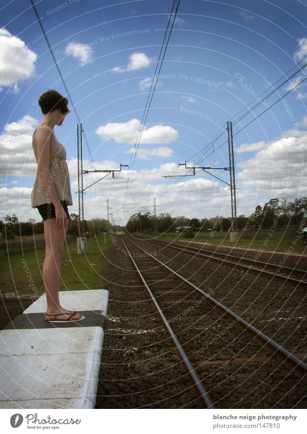 Woman Sky Blue Vacation & Travel Clouds Loneliness Lanes & trails Wait Railroad Hope Future Stand Desire Railroad tracks Rail transport Direction