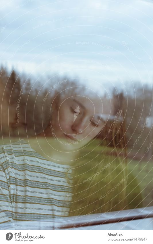 Young woman calmly looking down through a window pane Flat (apartment) Garden Window pane Youth (Young adults) Face 18 - 30 years Adults Landscape