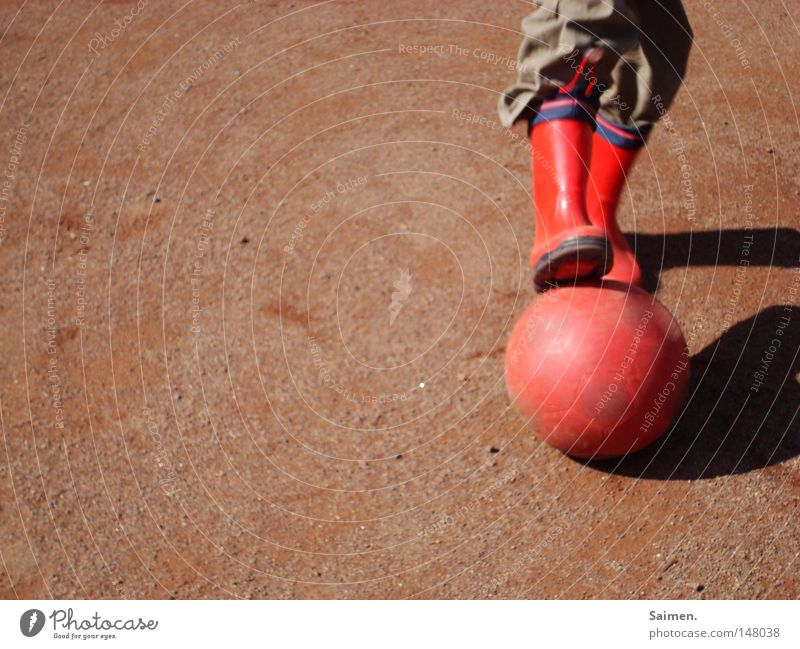 Football with passion Exterior shot Shadow Joy Playing Ball sports Football pitch Energy industry Pants Boots Rubber boots Poverty Dirty Red Power Passion